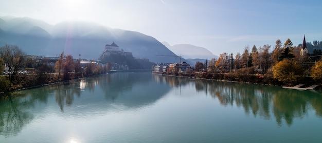 Panoramiczny widok na gładką powierzchnię rzeki przed twierdzą kufstein w austrii.