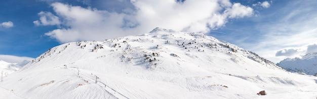 Panoramiczny widok na górski krajobraz pokryty śniegiem z błękitnym niebem i chmurami. miejsce na tekst.
