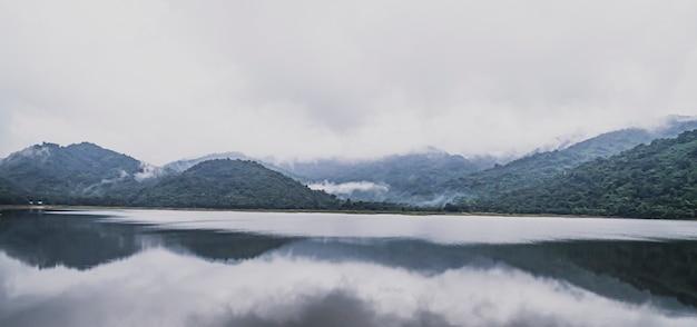 Panoramiczny widok na góry jezioro z tropikalnym lasem drzew. piękne spokojne jezioro z pasmami górskimi w tle. cudowny klimatyczny krajobraz