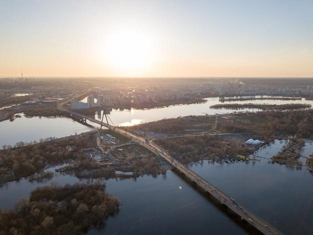 Panoramiczny widok na kijów i most północny z przejeżdżającymi samochodami przez rzekę dniepr. zdjęcie z drona