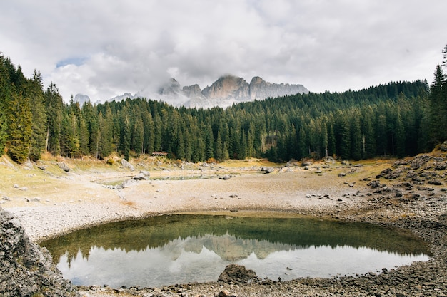 Panoramiczny widok na lago di carezza z odbiciami gór i nieba nad jeziorem
