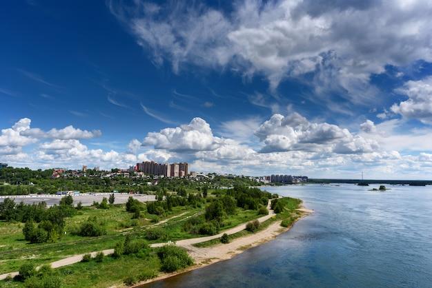 Panoramiczny widok na miasto irkuck i rzekę angarę od akademickiego mostu w słoneczny letni dzień z pięknymi chmurami