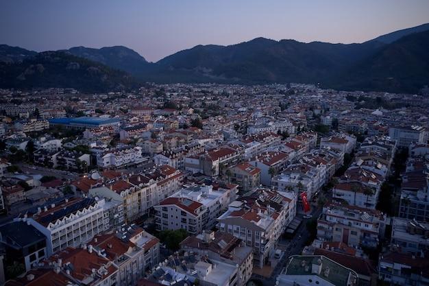 Panoramiczny widok na miasto marmaris o zachodzie słońca. widok z lotu ptaka domów z czerwonymi dachami i górami w tle. krajobraz miasta marmaris wieczorem.