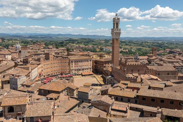 Panoramiczny widok na miasto siena z piazza del campo i torre del mangia to wieża w mieście z katedry w sienie (duomo di siena). letni słoneczny dzień i dramatyczne błękitne niebo