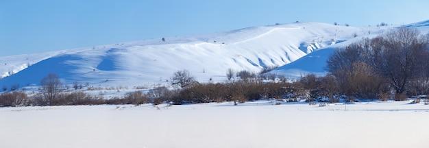Panoramiczny widok na ośnieżone wzgórza w centralnej rosji. zimowy słoneczny dzień.