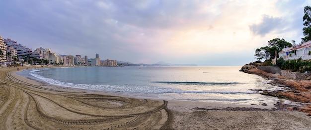 Panoramiczny widok na plażę o zachodzie słońca z budynkami wzdłuż brzegu i zachmurzonym niebem. calpe alicante.