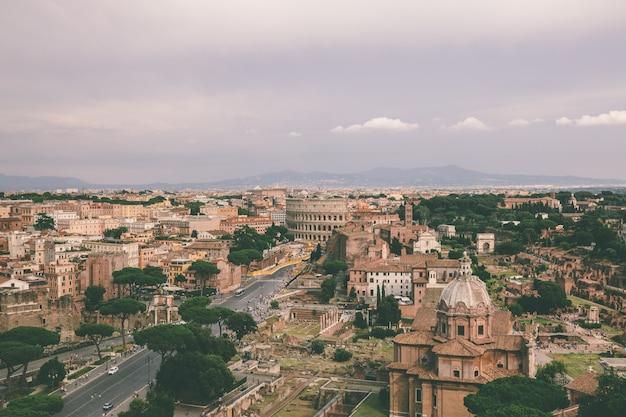Panoramiczny widok na rzym z rzymskim forum i koloseum z pomnika vittorio emanuele ii, znanego również jako vittoriano. letni słoneczny dzień i dramatyczne błękitne niebo