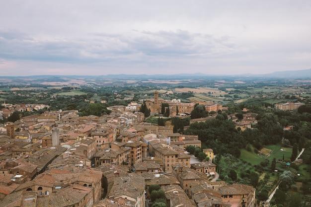 Panoramiczny widok na sienę z zabytkowymi budynkami i dalekimi zielonymi polami z torre del mangia to wieża w mieście. letni słoneczny dzień i dramatyczne błękitne niebo