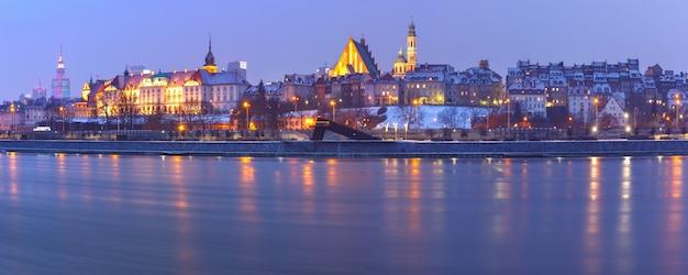 Panoramiczny widok na stare miasto z odbiciem w wiśle podczas wieczornej niebieskiej godziny, warszawa, polska.
