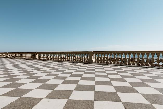 Panoramiczny widok na terrazza mascagni (taras mascagni) przed morzem liguryjskim na zachodnim wybrzeżu toskanii w livorno. ludzie chodzą i odpoczywają na tarasie?