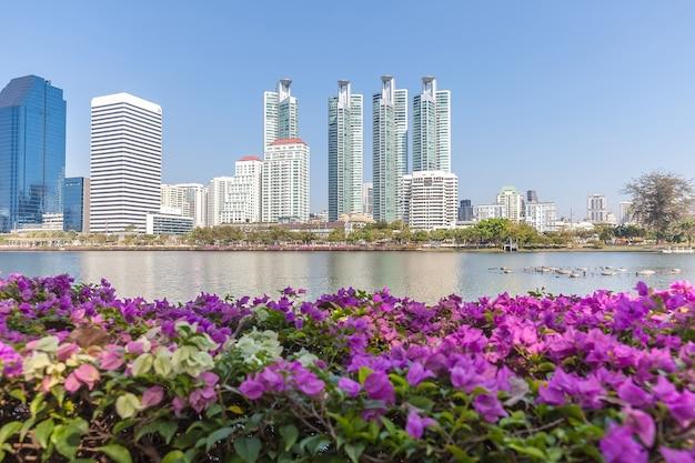 Panoramiczny widok na wieżowce miasta przez różowe kwiaty i duże jezioro