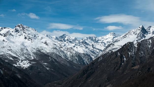 Panoramiczny widok na wysokie szczyty górskie i ośnieżone grzbiety na dużych wysokościach w alpach