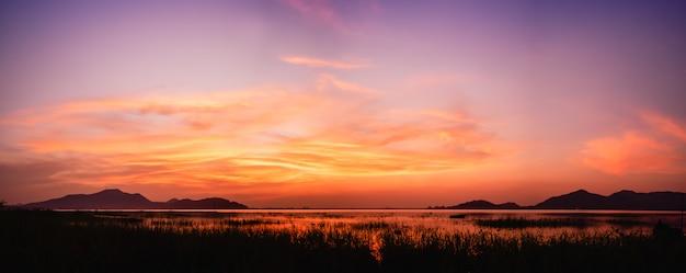 Panoramiczny widok na zachód słońca nad jeziorem z zmierzchu niebo