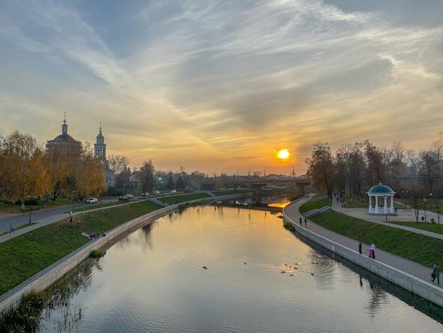 Panoramiczny widok na zachód słońca nad rzeką, promenadą, starymi kościołami na tle nieba z chmurami