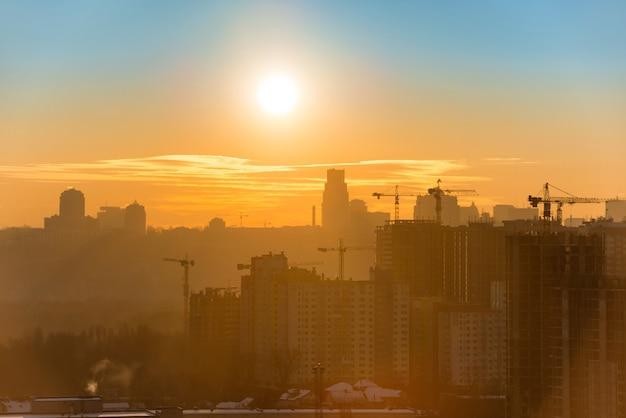 Panoramiczny widok na zachód słońca w mieście z sylwetką budynków i przemysłowych dźwigów