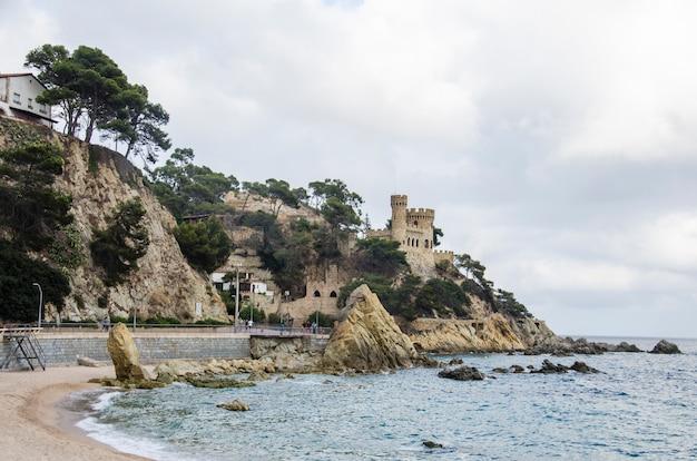 Panoramiczny widok na zamek lloret de mar o zachodzie słońca. antyczny forteca w lloret de mar, hiszpania. zamek sant joan.