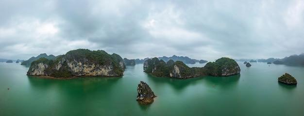 Panoramiczny widok na zatokę ha long, wietnam. pochmurno i nastrojowo. rozrzucone wapienne wyspy. widok z lotu ptaka.