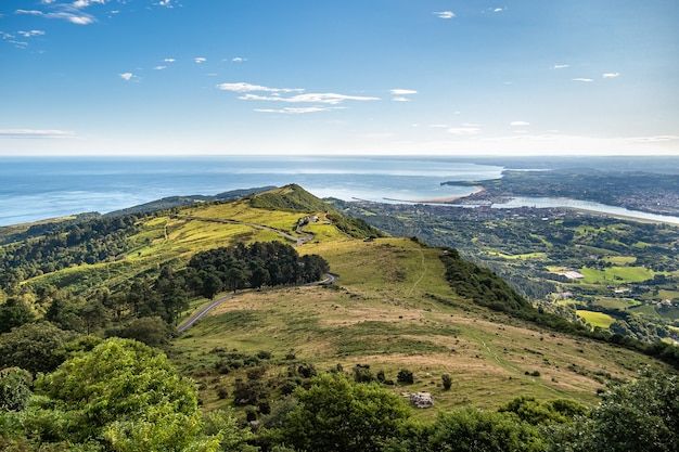 Panoramiczny widok na zielone wzgórze, morze i miasto oraz granicę między hiszpanią a francją. kraj basków wczesnym rankiem.