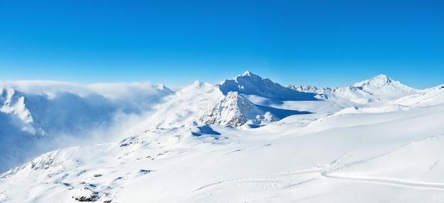 Panoramiczny widok na zimowe góry w błękitne niebo w regionie elbrus na kaukazie (rosja)