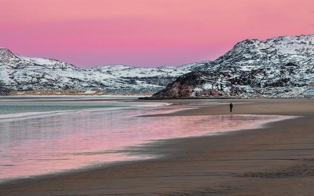 Panoramiczny widok na zimowy zachód słońca w niesamowitym kolorze magenty nad fiordem. widok na zimową teriberkę. rosja.