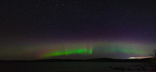 Panoramiczny widok na zorzę polarną. polarne światła w nocy gwiaździste niebo nad jeziorem.