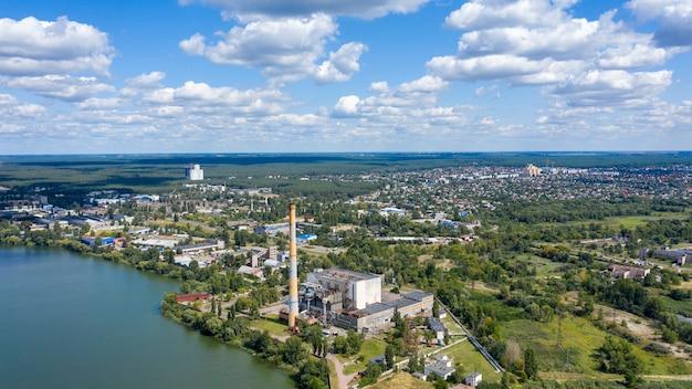 Panoramiczny widok obszaru przemysłowego fabryki lub zakładu z wieloma rurami lub kominami z dymem.