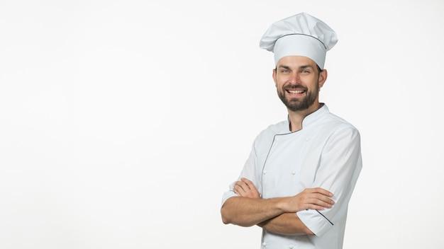 Panoramiczny widok szczęśliwy męski szef kuchni z jego ręką krzyżował przeciw białemu tłu
