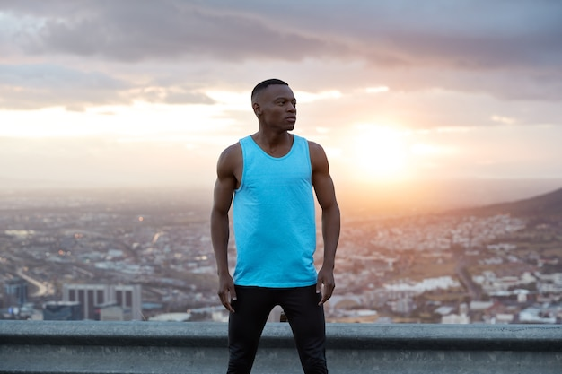 Panoramiczny widok wolnego czarnego muskularnego mężczyzny w odzieży sportowej, ma ćwiczenia na świeżym powietrzu, pozuje nad pięknym krajobrazem, wschód słońca o świcie, budynki miejskie, czyste niebo, cieszy się wolnością, świeżym powietrzem i samotnością