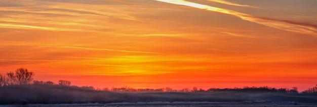 Panoramiczny widok wschodzącego słońca nad mglistą łąką