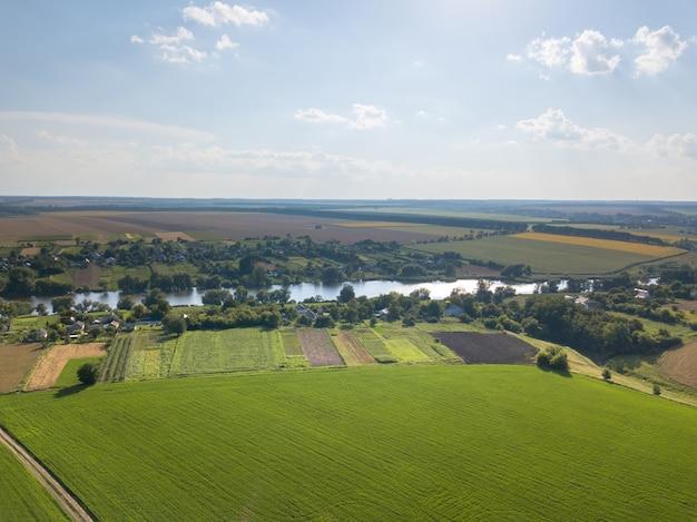 Panoramiczny widok z drona, zdjęcia lotnicze krajobrazu z zielenią lasów, pól uprawnych na tle zachmurzonego nieba o zachodzie słońca.