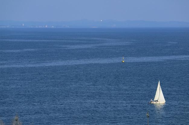 Panoramiczny widok z lotu ptaka na białą żaglówkę na błękitnym spokojnym morzu