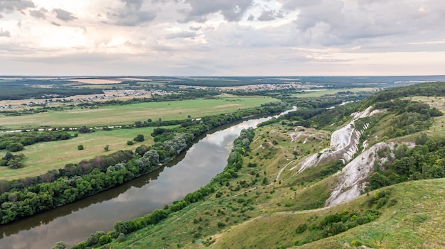 Panoramiczny widok z lotu ptaka na letni krajobraz zielonego pola uprawnego, wzgórz lub gór, dużą rzekę i pas leśny o zachodzie słońca