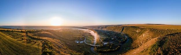 Panoramiczny widok z lotu ptaka na stary orhei o zachodzie słońca w dolinie z wioską rzeki i mgły