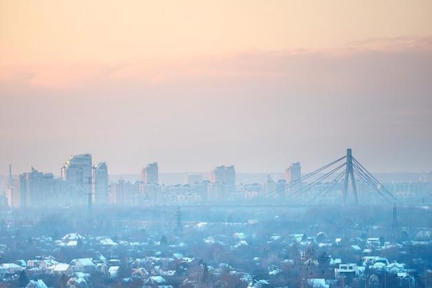 Panoramiczny widok zachodu słońca w mieście z mostem nośnym i budynkami