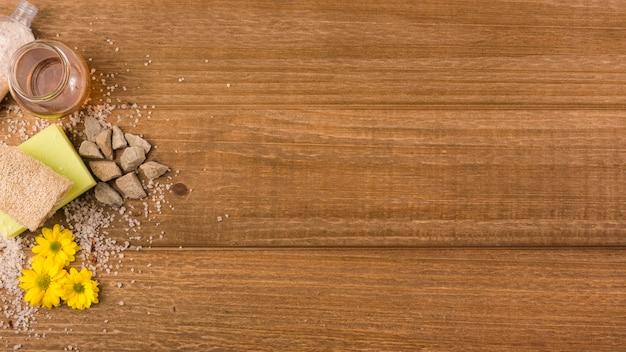 Panoramiczny widok żółtych kwiatów; sól; kamienie; gąbka; butelka loofah i miód na drewniane teksturowanej tło