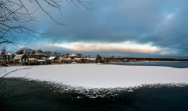 Panoramiczny zimowy widok ze starymi domami w pobliżu pokrytego śniegiem jeziora. autentyczne północne miasto kem zimą. rosja.