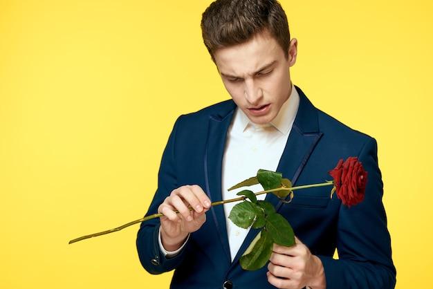 Panowie w klasycznym garniturze na żółtym kosmosie i czerwonej róży romantycznej przycięty portret modelki.