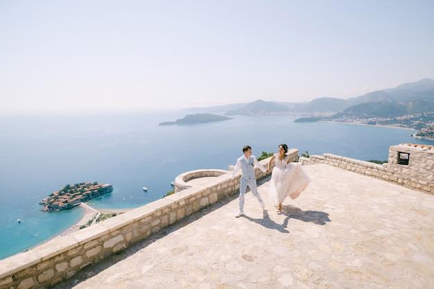 Państwo młodzi biegają trzymając się za ręce na tarasie widokowym z widokiem na wyspę