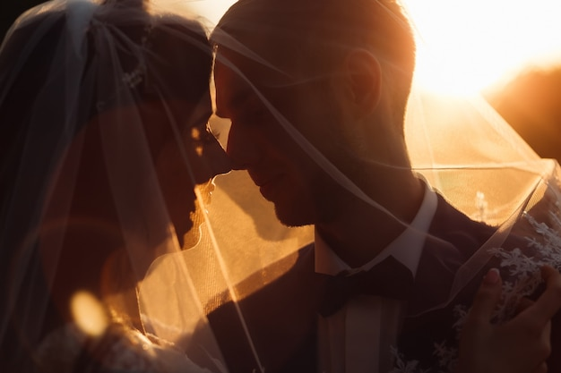 Państwo młodzi chcą się całować i okryć welonem. wieczorne słońce oświetla nowożeńców.