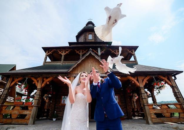 Państwo młodzi chwytów gołębie stoi przed drewnianym kościół