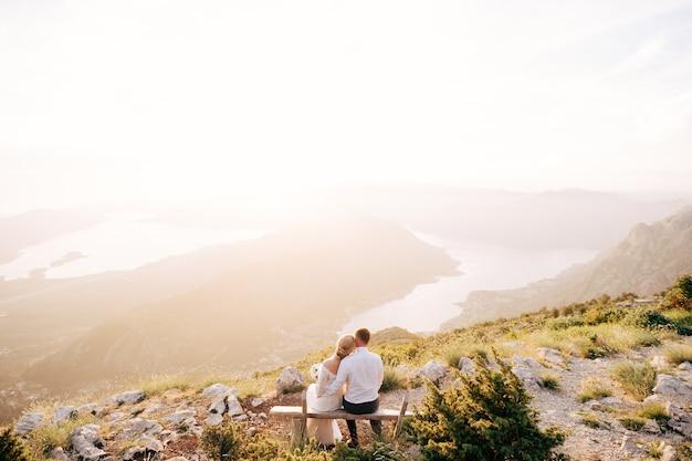 Państwo młodzi czule obejmują się i siedzą na drewnianej ławce w górach