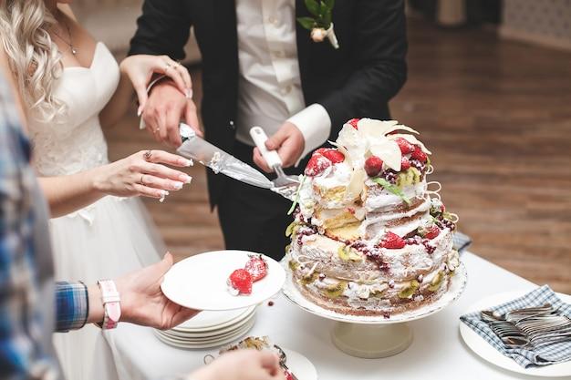 Państwo młodzi kroją tort weselny.