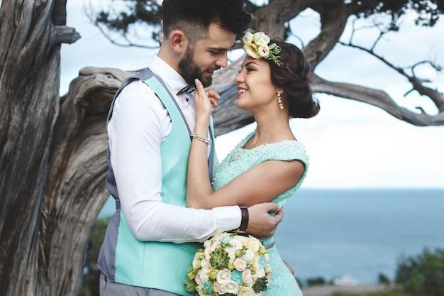 Państwo młodzi na naturze w górach blisko wody. kolor garnituru i sukienki tiffany. pocałunek i przytulenie.