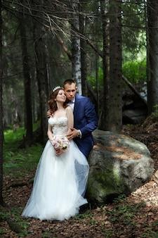 Państwo młodzi obejmują się i całują w ciemnym lesie w słońcu. ślub w naturze