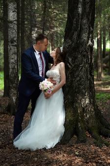 Państwo młodzi obejmują się i całują w ciemnym lesie w słońcu. ślub w przyrodzie, portret zakochanej pary w parku