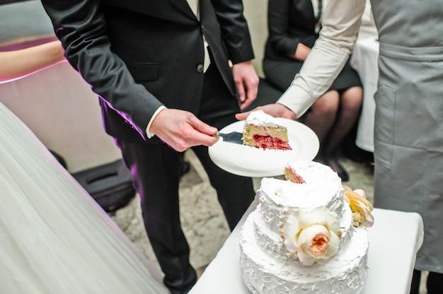 Państwo młodzi przecinają tradycyjny tort weselny