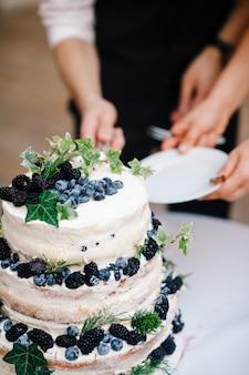 Państwo młodzi rżnięty ślubny tort z czarnymi jagodami
