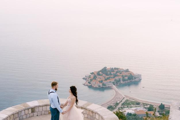 Państwo młodzi stoją i trzymają się za ręce na tarasie widokowym z widokiem na wyspę