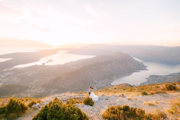 Państwo młodzi stoją na szczycie góry lovcen z widokiem na zatokę kotorską w pobliżu drewnianej ławki