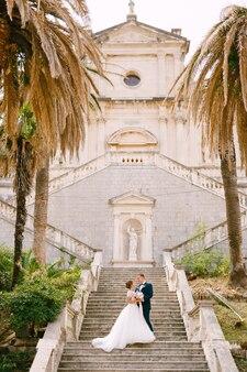 Państwo młodzi stoją przytuleni na schodach kościoła narodzenia najświętszej marii panny w
